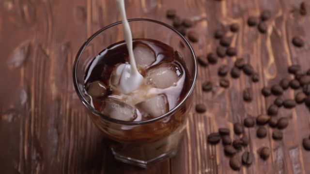 vídeos de stock e filmes b-roll de top view slow motion of cream being poured into a glass of cold brew iced coffee on brown wood table with coffee beans and cookies on black background - café gelado