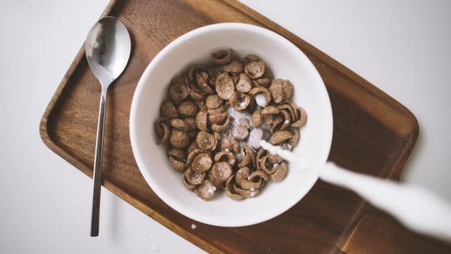 vídeos y material grabado en eventos de stock de vista superior disparo a cámara lenta de vertido de leche en cereal esel desayuno en un tazón blanco de escamas y leche con mesa de cuchara en bandeja de madera en la mesa de comedor - cuenco