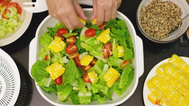 top view speed up hand mixing fresh vegetable salad into white bowl on countertop in kitchen video