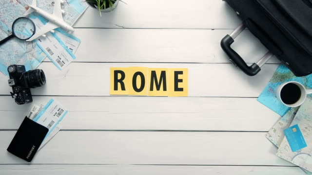 "top view time lapse hands laying on white desk word ""rome"" decorated with travel items - parola video stock e b–roll"