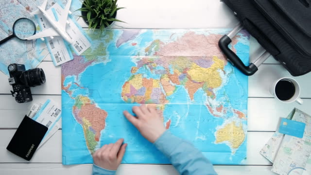 Top view traveler's hands picking a country for travelling at white wooden desk video