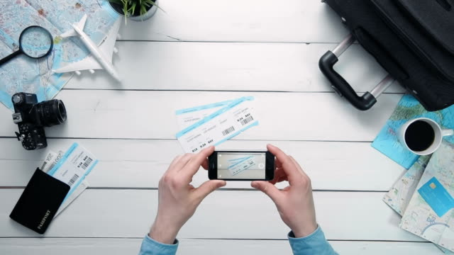 Top view traveler's hands taking a picture of airplance tickets with smart phone at white wooden desk video