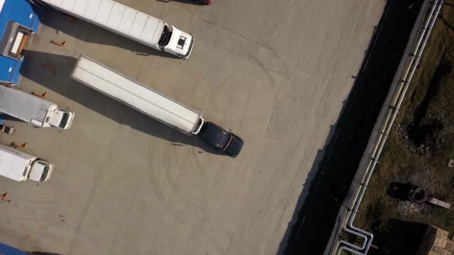 top view truck with freight container parking for unloading in storage building - тягач с полуприцепом стоковые видео и кадры b-roll