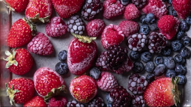 Top view variety of forest fruits, berries freezing, time lapse