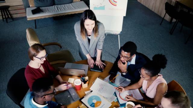 ansicht von oben frau chef büro teambesprechung führt. gemischter ethnischer herkunft kollegen betrachten marktforschung daten diagramme 4k - reisebüro stock-videos und b-roll-filmmaterial