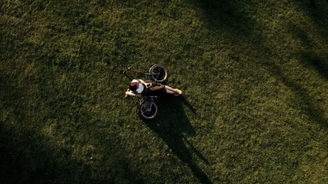 top view woman cyclist lying on green grass in city park and using mobile phone - ragazza auricolari rossi video stock e b–roll