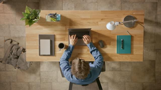 översta vyn zooma in shot: affärsman sitter vid trä skrivbordet fungerar på en bärbar dator i sitt hemmakontor. han dricker kaffe, typer, skriver e-post, surfar på internet, mönster programvara, online shopping - direkt ovanför bildbanksvideor och videomaterial från bakom kulisserna