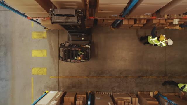 top-down aerial drone shot: elektrostapler-lkw-betreiber hebt palette mit karton-box in einem großen einzelhandelslager ein regal. logistik produkt- und warenliefer- und distributionszentrum - halle gebäude stock-videos und b-roll-filmmaterial