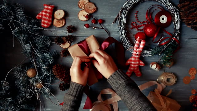 A top-down plan. Fully visible the table with the decorations. Female hands put and finalize Christmas gift wrapped in craftool paper on a wooden table. Bandaging tape and tied in a bow video