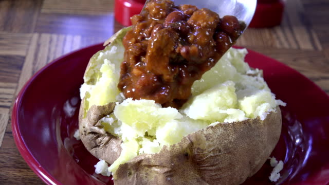 Topping a baked potato with chili con carne video