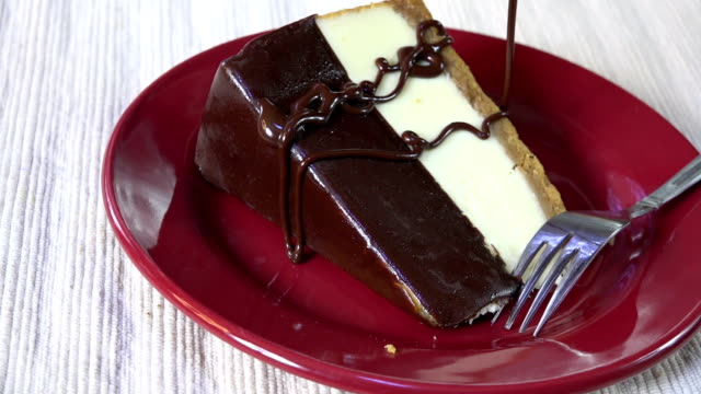 topping a cheesecake with chocolate sauce - sernik filmów i materiałów b-roll