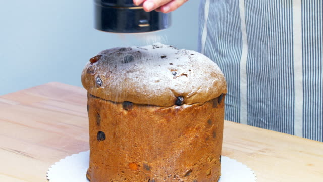 topping christmas panettone with powdered sugar - panettone video stock e b–roll