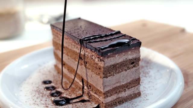 slo mo ld topping slice of cake with chocolate dressing - desserts stock videos and b-roll footage