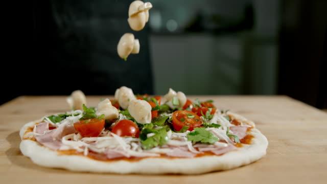 slo mo topping die pizza mit frischen champignons - selbstgemacht stock-videos und b-roll-filmmaterial