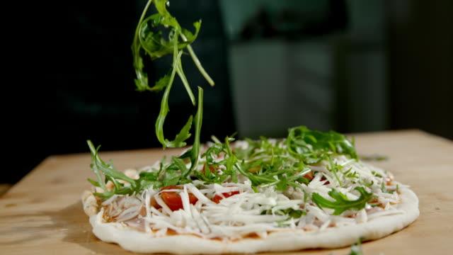 vídeos y material grabado en eventos de stock de slo mo encabezando la pizza con frescas hojas de cohete - comida casera