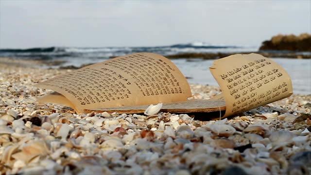 tora-seite am strand. alten papyrus nachricht von thora buch - schriftrolle stock-videos und b-roll-filmmaterial