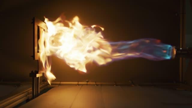 ein fackelfeuer an einem robotikarm mit fabric während eines flammrückhaltestests (produktforschung und-entwicklung) in einer indoor-fertigungsanlage - fackel stock-videos und b-roll-filmmaterial