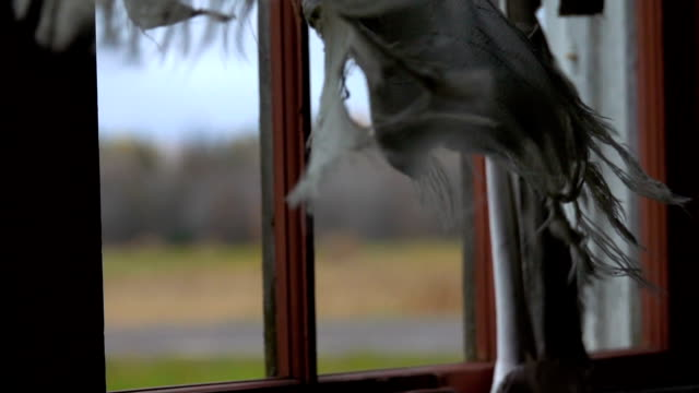 SLOW MOTION: Torn curtains on the windows of a ruined house swaying in the wind video