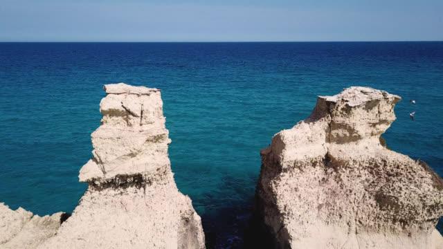 torre dell'orso, lecce, puglia, italy. path in the gap near two rocks, drone video - lecce video stock e b–roll