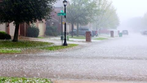 vidéos et rushes de tempête de pluie torrentielle avec la grêle dans la rue résidentielle urbaine - pluie