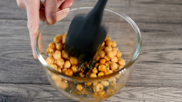 tossing chickpea with paprika and parsley dressing - paprica video stock e b–roll