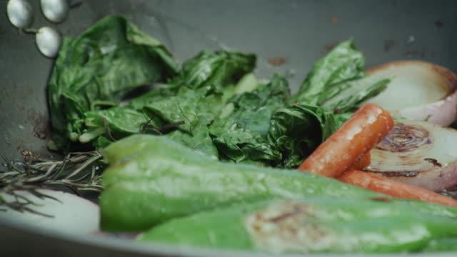 tossing  vegetables mix in a frying pan on open flame - лимонный сок стоковые видео и кадры b-roll