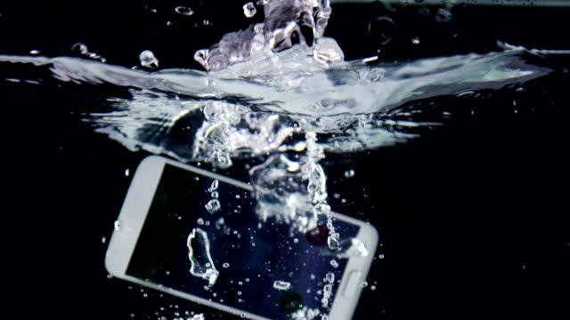 touchscreen-smartphone mit eingehenden anruf auf dem display, die ins wasser fallen - nass stock-videos und b-roll-filmmaterial