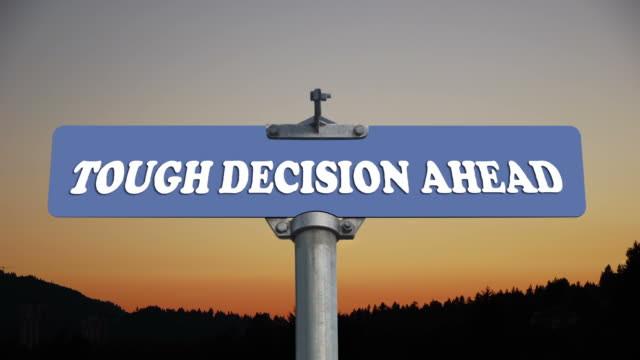 Tough decision ahead road sign with flowing clouds video