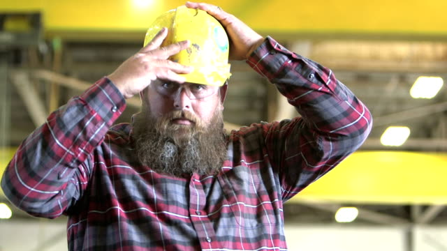 Tough man with beard puts on hardhat A tough-looking, heavyset man with a long beard, staring at the camera. He is a worker standing in a warehouse, wearing a plaid shirt and safety glasses.  He puts on a hardhat and crosses his arms over his wide chest. protective workwear stock videos & royalty-free footage