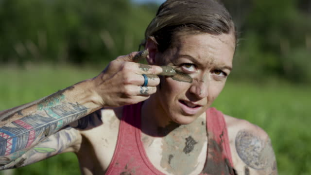 Tough Mudder A woman stares directly into the camera after a mud run. She looks serious and intense as she puts a line of  mud as war paint on her face under both her eyes. conquering adversity stock videos & royalty-free footage