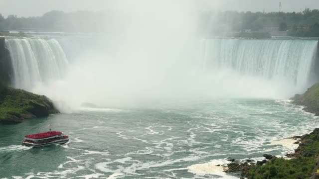 tour ferry floats by the horseshoe falls in the summer - niagara falls stock videos & royalty-free footage