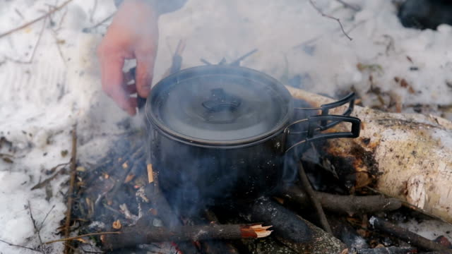 tourism, a man puts the bars in the fire, cooks soup in the campaign, video