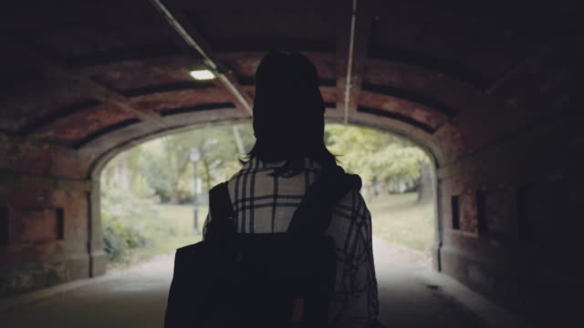 Tourism and Vacation In Central Park. New York City Beautiful young woman walking in tunnel in Central Park. Manhattan. New York City. USA central park manhattan stock videos & royalty-free footage