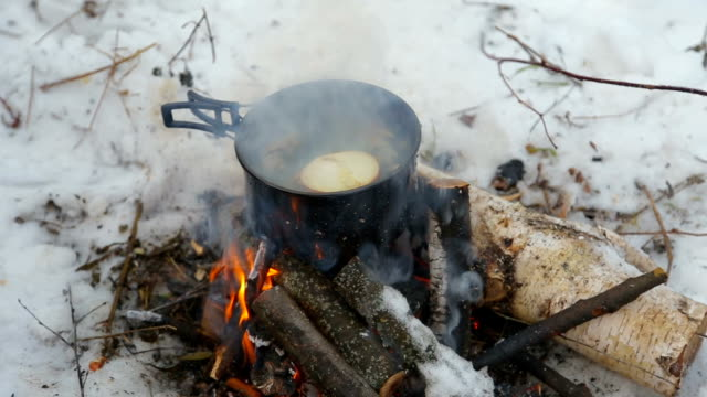 tourism, fish soup is cooked at the stake in a hike video