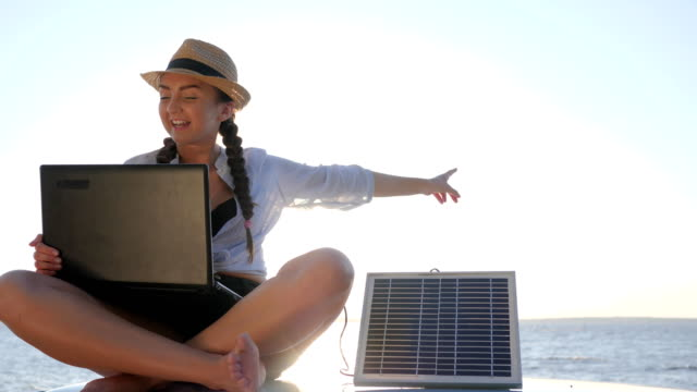 tourism, girl sits on car roof in backlight speaks on laptop and recharges solar array, young woman sitting on vintage car video