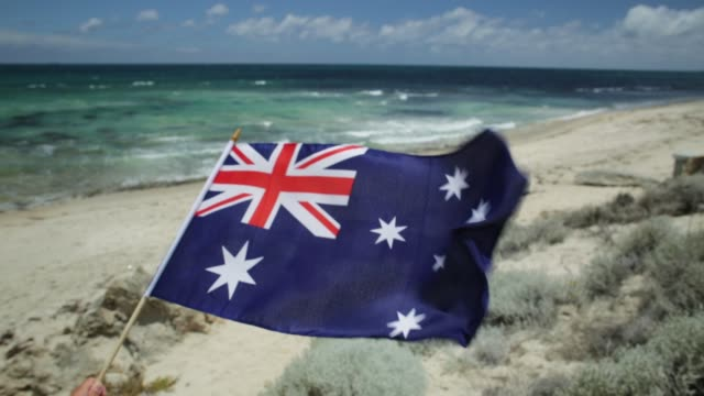 Tourism in Australia Australian flag waving on the foreground with coastal landscape of Mettams Pool, Trigg Beach, North Beach near Perth in Western Australia. Tourism in Australia. natal stock videos & royalty-free footage