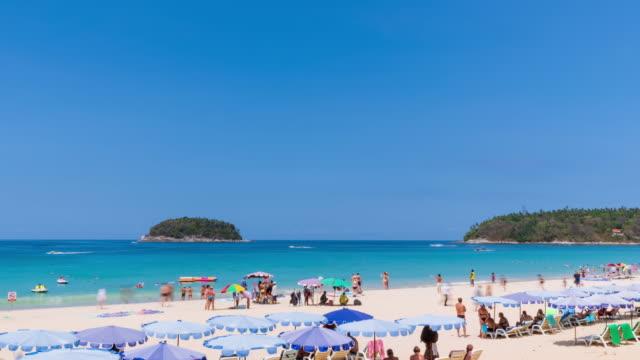 vidéos et rushes de tourisme et cristal clair turquoise bleu mer à kata beach, destination de voyage célèbre à phuket, thaïlande; panoramique à droite - time lapse - mer d'andaman