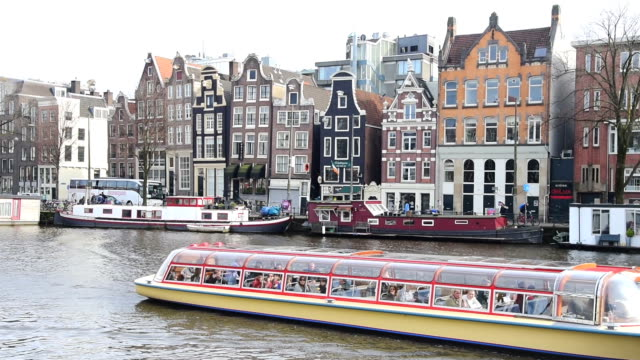 tourist and street traffic tram & boats at amsterdam central station  amsterdam, netherlands - amsterdam video stock e b–roll