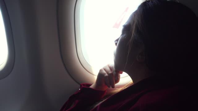 vídeos y material grabado en eventos de stock de turista asiática mujer mirando ventana de avión durante el vuelo - viaje en primera clase