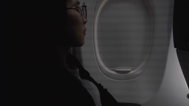 tourist asian woman opens the airplane window light into cabin travel concept - sedili aereo video stock e b–roll