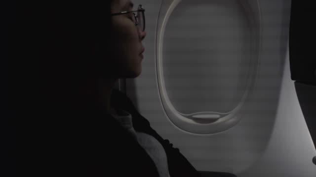 vídeos y material grabado en eventos de stock de turista asiática mujer abre la luz de la ventana del avión en cabina viaje concepto - viaje en primera clase