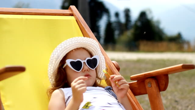 tourist baby girl is sitting on a deck chair. baby girl with sunglasses and a hat eats cand y and relaxes on a journey. - cappello video stock e b–roll