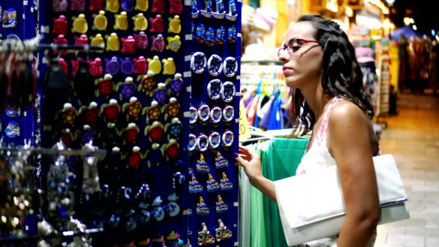 Tourist buying souvenirs Young woman looking at magnets souvenirs at street store. souvenir stock videos & royalty-free footage