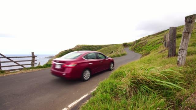 観光車のマウイ島のハナへの海洋側道沿いを運転します。ハワイ旅行の休暇。美しい緑の風景と自然。 - 曲線点の映像素材/bロール
