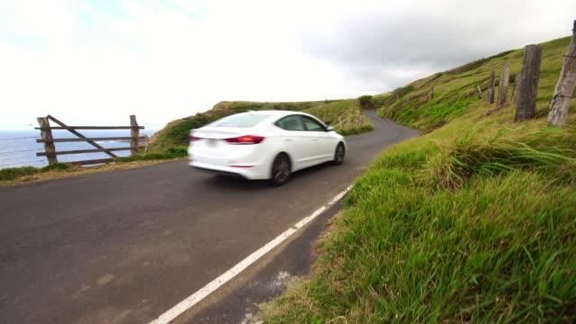 マウイ島のハナへの道路上の海岸線に沿って運転観光車。ハワイ旅行の休暇。美しい緑の風景と自然。 - 曲線点の映像素材/bロール