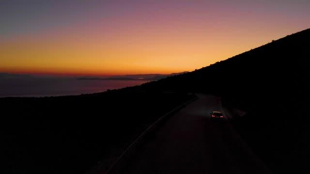 drone: tourist car exploring the untouched island in greece at early dawn. - viaggio in macchina video stock e b–roll