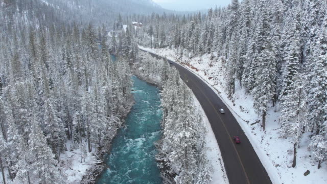 AERIAL: Tourist cars cruising through snowy woods and along a emerald river.