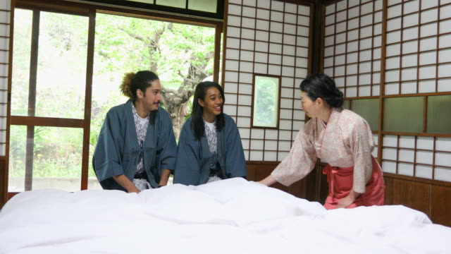 Tourist Couple Being Shown How to Make a Japanese Bed
