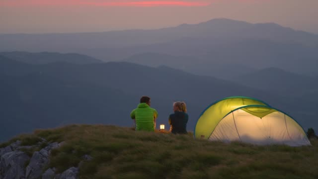 slow motion: tourist couple camping in the alps sit by the lantern and talk on a calm evening - date night stock videos & royalty-free footage