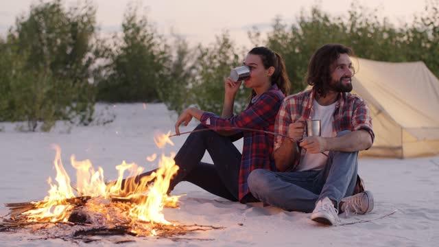vídeos de stock e filmes b-roll de tourist couple camping near campfire outdoors on the nature - caneca